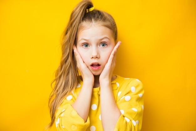 Closeup portrait de fille enfant excité touchant ses joues sur fond jaune