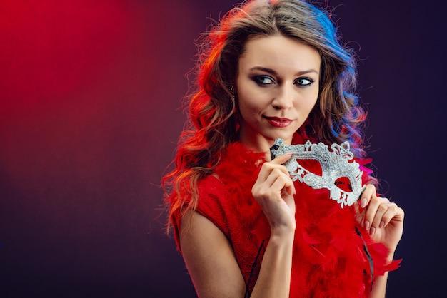 Closeup portrait d'une fille sexy tenant un masque dans ses mains