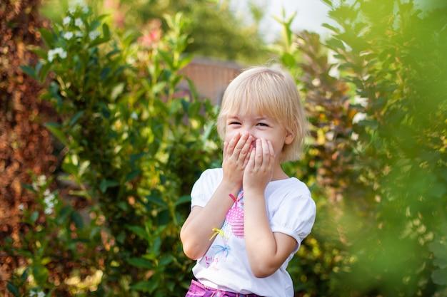 Closeup portrait de fillette blobde heureuse à l'école primaire en plein air dans un parc verdoyant