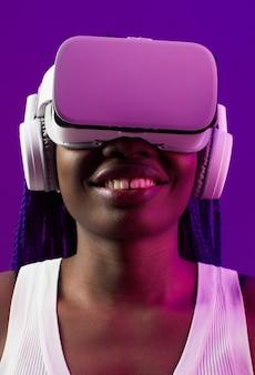 Closeup portrait futuriste d'une jeune femme afro-américaine portant un casque vr sur fond violet