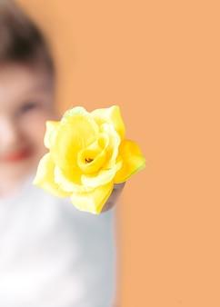 Closeup portrait garçon souriant heureux avec orange rose.