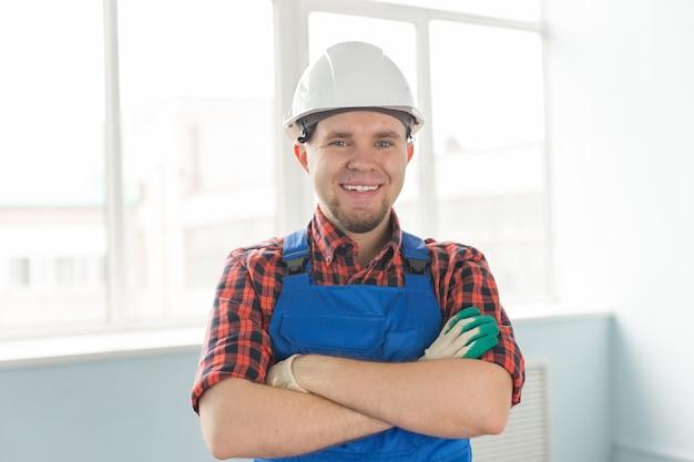 Closeup portrait d'heureux constructeur mâle caucasien portant un casque blanc.