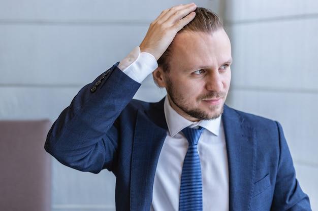Closeup portrait d'un homme en costume à la recherche de suite et se toucher la tête