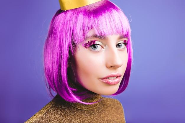 Closeup portrait incroyable jeune femme à la mode avec des cheveux violets coupés. maquillage lumineux, guirlandes, robe de luxe, fête, anniversaire, grande fête, vraies émotions.