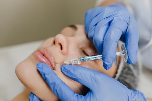 Closeup portrait injection sur les lèvres de jolie femme pendant les procédures de botox dans le salon. travail professionnel, rajeunissement, médecine moderne, fabrication de beauté, soins de santé
