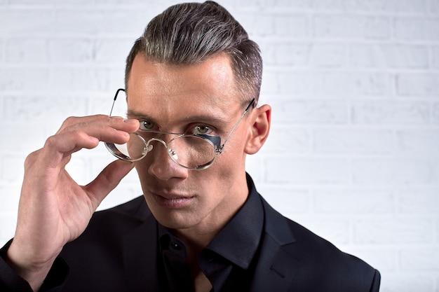 Closeup portrait jeune bel homme d'affaires avec des lunettes, debout sur le mur de briques