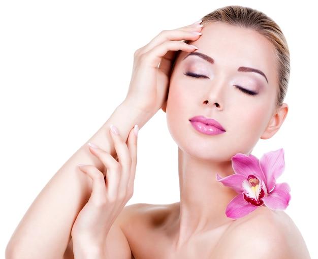 Closeup portrait de jeune belle fille avec une fleur près du visage - isolé sur un mur blanc