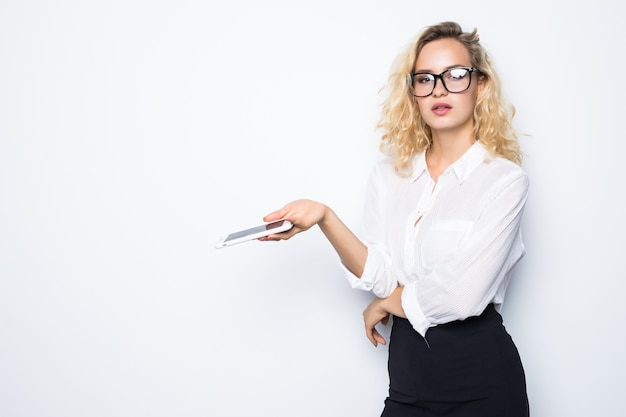 Closeup portrait jeune femme d'affaires malheureuse, ennuyée par quelque chose, quelqu'un sur son téléphone portable tout en envoyant des sms, recevant de mauvais sms, message texte, mur blanc isolé.