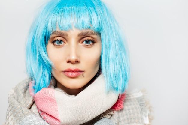 Closeup portrait de jeune femme aux yeux et coiffure bob bleu.