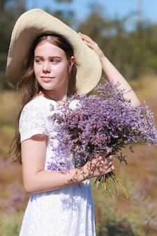 Closeup portrait d'une jeune femme chapeau de paille avec un bouquet de fleurs sauvages.