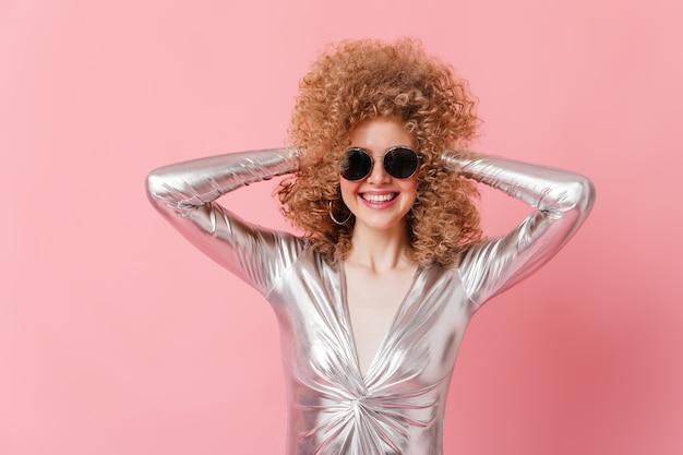 Closeup portrait de jeune femme en chemisier argenté et lunettes de soleil ébouriffant ses cheveux.