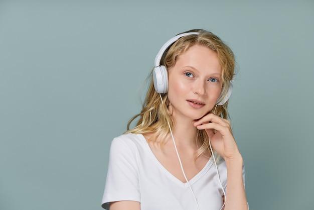 Closeup portrait de jeune femme yeux fermés écouter de la musique via un casque sur un mur de couleur gris neutre.