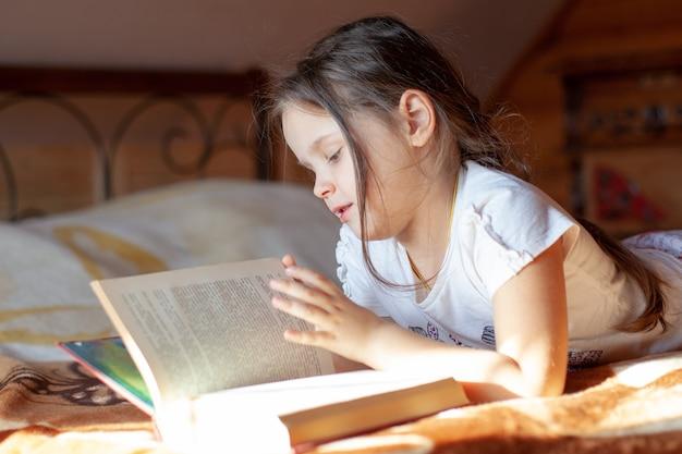 Closeup portrait d'une jeune fille lisant un livre feuilletant les pages dans la maison de village en rondins