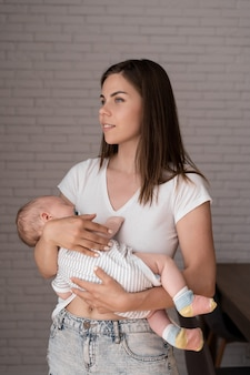 Closeup portrait d'une jeune maman. une femme tient un nouveau-né dans ses bras.