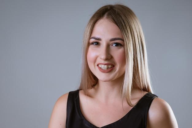 Closeup portrait d'une jolie femme avec des dents tordues sur un mur léger
