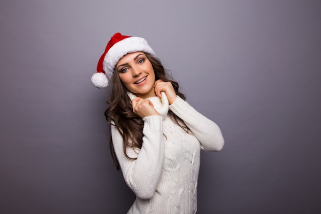 Closeup portrait d'une jolie femme de noël avec un chapeau de père noël rouge, robe blanche, souriant, heureux, en attente de vacances. émotion positive sur mur gris isolé.