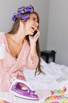Closeup portrait jolie fille aux cheveux longs en peignoir rose et bigoudi sur la tête au repassage des vêtements à la maison. elle parle au téléphone, rit et a l'air appréciée.