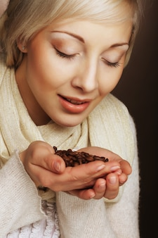 Closeup portrait de jolie fille blonde tenir les grains de café torréfiés à chaud dans les mains