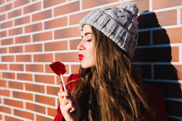 Closeup portrait jolie fille brune aux cheveux longs sur le mur extérieur. elle porte un bonnet tricoté, garde les yeux fermés, envoie un baiser aux lèvres rouges de sucette.