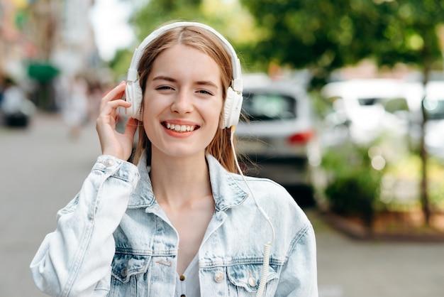 Closeup portrait de jolie fille souriante dans des écouteurs en plein air