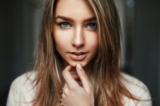 Closeup portrait d'une jolie jeune femme aux yeux bleus incroyables