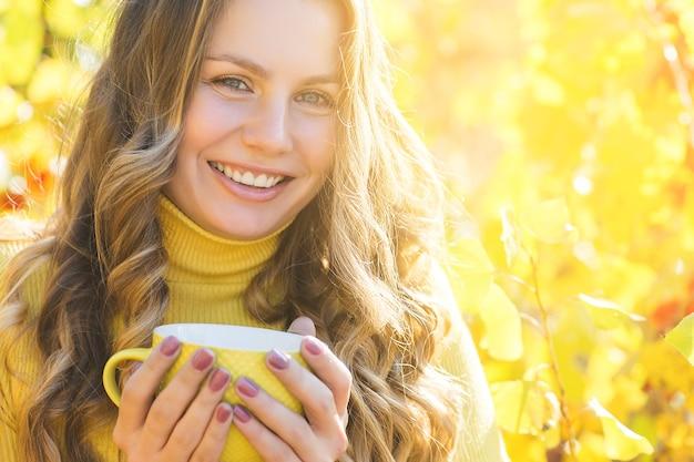 Closeup portrait de jolie jeune femme sur fond d'automne. belle femelle blonde sur fond d'automne à l'extérieur.