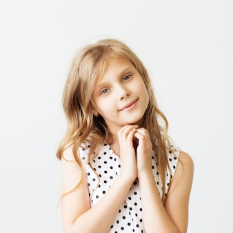Closeup portrait d'une jolie petite fille en face de fond blanc