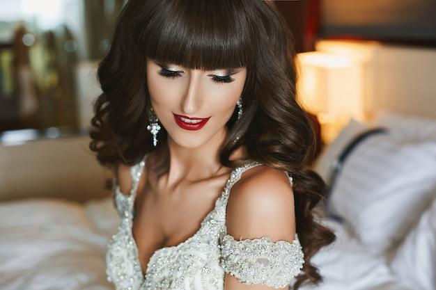 Closeup portrait d'une magnifique jeune mariée avec une coiffure de mariage et des lèvres rouges en robe de mariée. jeune femme dans une robe de mariée de luxe décorée de cristaux. mode de mariage