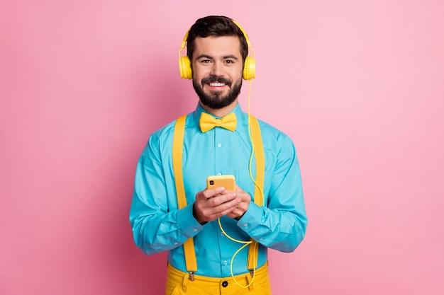 Closeup portrait de mec barbu tenir le téléphone porter des écouteurs écouter de la musique