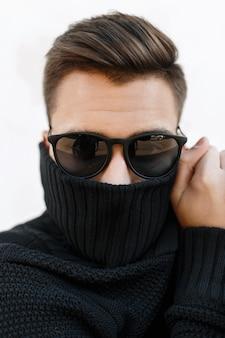 Closeup portrait de mode d'un jeune beau mec avec une coiffure élégante à lunettes de soleil