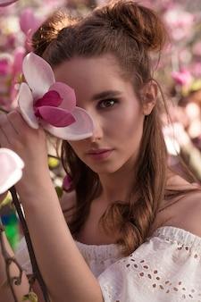 Closeup portrait de modèle brune élégante posant dans un jardin de magnolia en fleurs