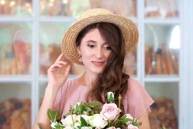 Closeup portrait of attractive young girl in dress et chapeau de paille tenant un bouquet de fleurs