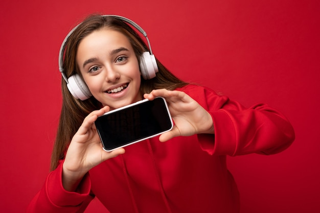 Closeup portrait of beautiful brunette girl wearing red hoodie isolé sur fond rouge holding