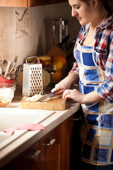 Closeup portrait of brunette woman couper le chou avec un couteau