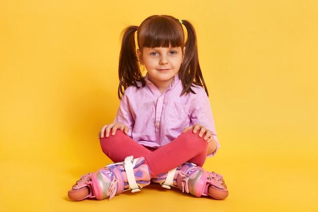 Closeup portrait of calm little girl sitting on floor avec les jambes croisées