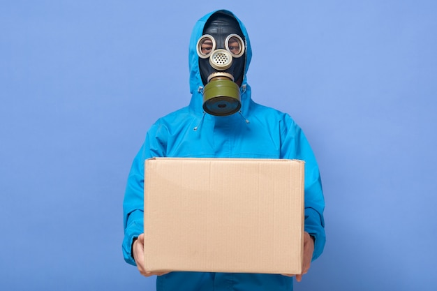 Closeup portrait of chemical scientist wearing uniform and gas mask holding carton box in hands