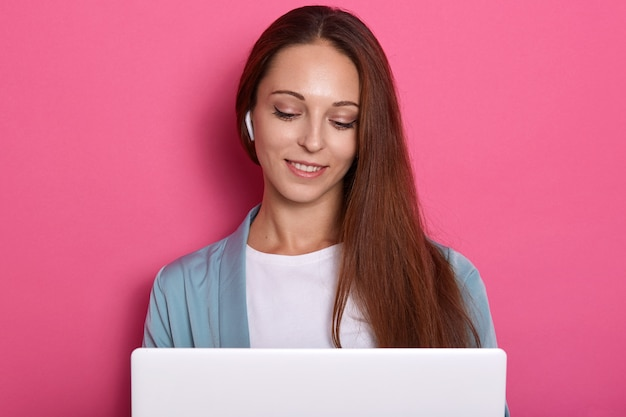 Closeup portrait of concentré smiling girl working with lap top