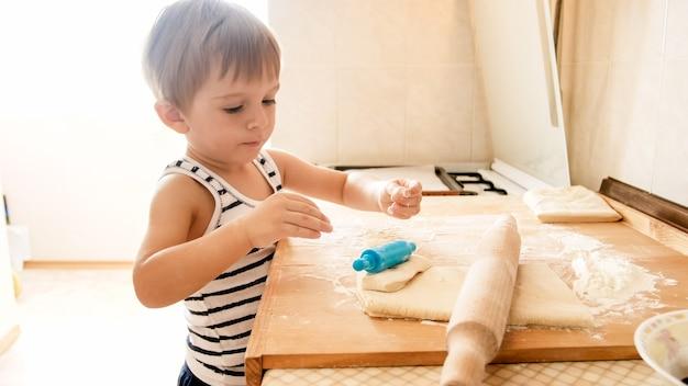 Closeup portrait of cute 3 ans bébé garçon debout sur la cuisine et la cuisson de la pâte