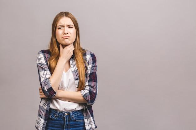 Closeup portrait of cute malade jeune femme blonde en casual ayant mal à la gorge, tenant la main sur son cou / douleur à la gorge, concept de déglutition douloureuse / inflammation des voies respiratoires supérieures.
