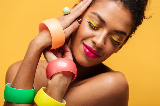 Closeup portrait of fashion afro american woman with bright makeup and multicolour accessories holding hands at face, isolated over yellow wall