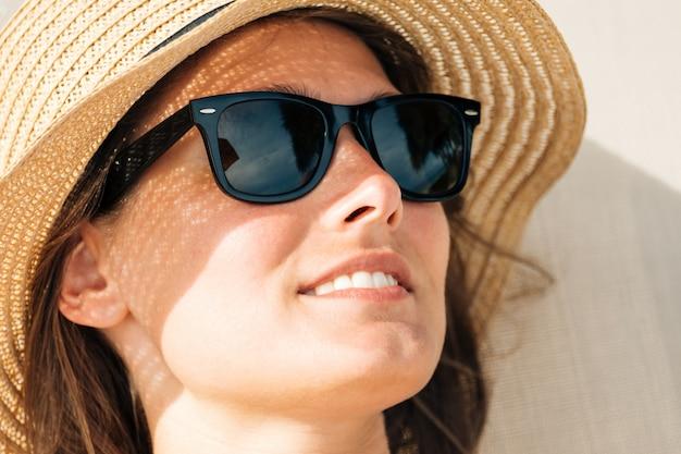 Closeup portrait of a female cache son visage du soleil sous un chapeau de paille