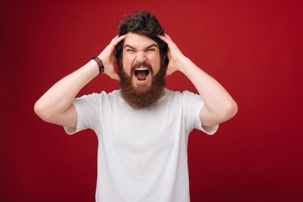 Closeup portrait of handsome en colère désespéré, stressé homme barbu frustré sur mur rouge