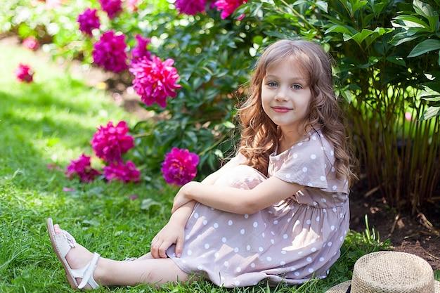 Closeup portrait of happy blonde petite fille aux longs cheveux bouclés et dans un béret avec bouquet de pivoines roses. notion d'enfance. fête. enfant mignon avec des fleurs pour la fête des mères. fête.