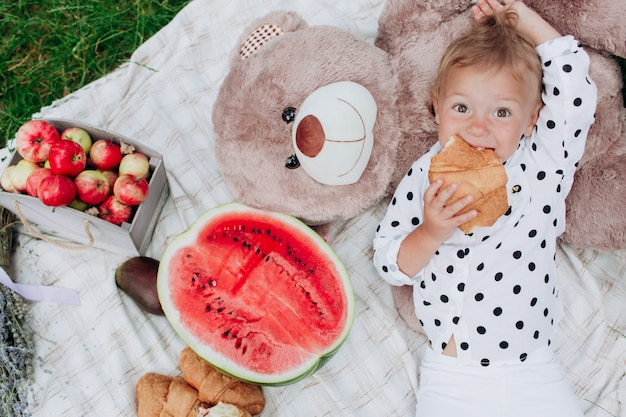 Closeup portrait of happy little girl smiling and allongé sur la couverture à l'herbe, profitant de l'été en plein air. adorable enfant s'amusant et se détendant pendant le pique-nique avec sa famille dans le parc.