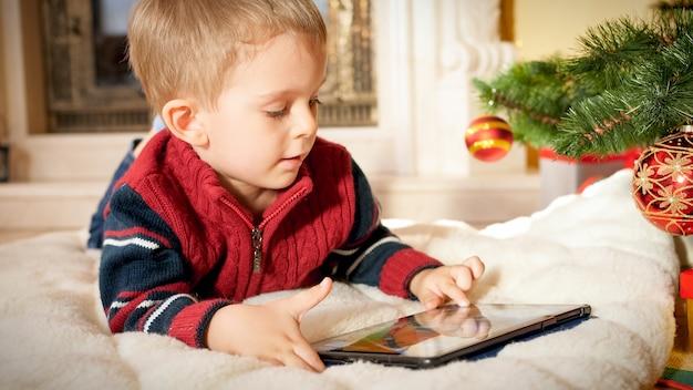 Closeup portrait of happy smiling little boy using digital tablet computer en position couchée sur le sol sous l'arbre de noël au salon
