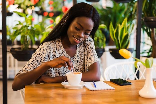 Closeup portrait of happy young black woman buvant du café au café