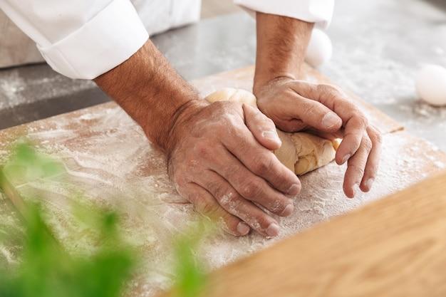 Closeup portrait of man chef faire de la pâte pour le pain, sur la table à la boulangerie ou la cuisine