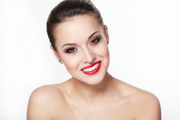 Closeup portrait of sexy smiling caucasian young woman model with glamour red lips, bright makeup, eye arrow makeup, purity teint. une peau parfaitement propre, des dents blanches