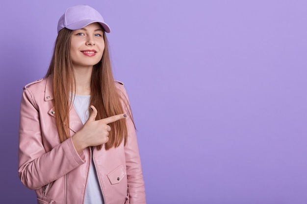 Closeup portrait of smiling caucasian student female wearing pink pale leather jacket and cap