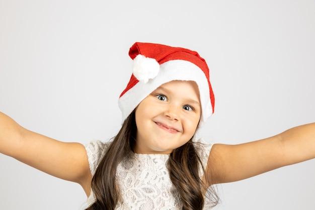 Closeup portrait of smiling funny girl in santa claus hat prenant selfie isolé sur fond blanc...